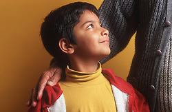 Side profile of young boy looking up at adult who has arm around his shoulder,
