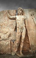 Close up of a Roman Sebasteion relief  sculpture of Ares, Aphrodisias Museum, Aphrodisias, Turkey.  Against a grey background.<br /> <br /> The nude and classically7 styled young god wears only a helmet and holds a spear (missing) in one hand and a shield in the other. At the left stands cuirass, and at the upper right corner hangs his sword. Ares was a god of war and was not later defaced by Christians probably because he so closely resembles a young emperor. .<br /> <br /> If you prefer to buy from our ALAMY STOCK LIBRARY page at https://www.alamy.com/portfolio/paul-williams-funkystock/greco-roman-sculptures.html . Type -    Aphrodisias     - into LOWER SEARCH WITHIN GALLERY box - Refine search by adding a subject, place, background colour, museum etc.<br /> <br /> Visit our ROMAN WORLD PHOTO COLLECTIONS for more photos to download or buy as wall art prints https://funkystock.photoshelter.com/gallery-collection/The-Romans-Art-Artefacts-Antiquities-Historic-Sites-Pictures-Images/C0000r2uLJJo9_s0