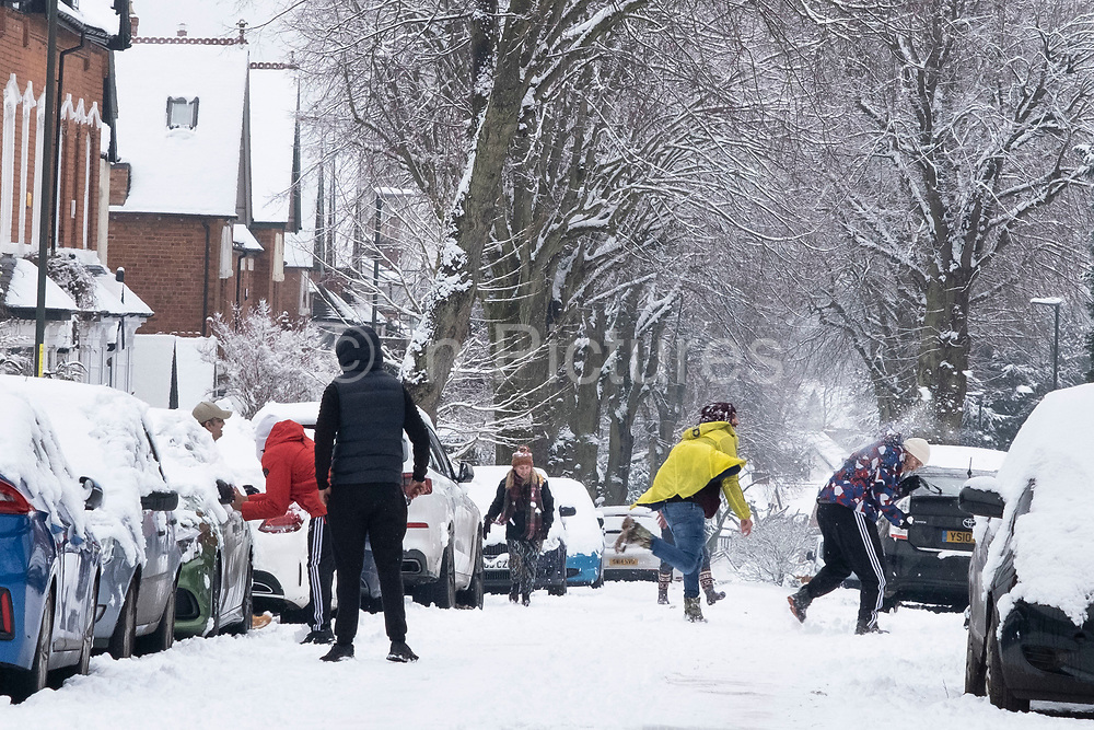 Local people out and about enjoying a snowball fight in the snow in Moseley on 24th January 2021 in Birmingham, United Kingdom. Deep snow arrived in the Midlands giving some light relief and fun during the current lockdown for people who simply enjoyed the weather.