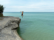 """A boy jumps into Lake Superior..  Image from the area known as """"The Cove,"""" Pictured Rocks National Lakeshore, Michigan, USA."""