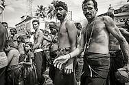 Hinduiska pilgrimer, på väg till det heliga templet i Sabarimala, dansar på gatorna i den indiska staden Erumely i Kerala. För att helt uppgå i pilgrimsvandringen, ge upp sitt eget ego och för att hedra Lord Ayyappa, målar pilgrimerna sina kroppar och bär vapen i trä. Traditionen kallas pettatullal. Både hinduer och muslimer anser att Erumely är en helig stad.  <br /> <br /> Sabarimala pilgrims are dancing on the streets of Erumely in the Kottayam district of Kerala, India. In order to give up their egos and to surrender to Lord Ayyappa, the Hindu pilgrims paint their bodies and carry weapons made of wood on the way to Sabarimala. Erumely is considered holy by both Hindus and Muslims.<br /> <br /> Copyright 2016 Christina Sjögren, All Rights Reserved