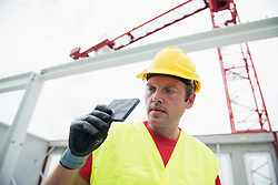 Worker examining construction material at site, Munich, Bavaria, Germany, Europe