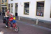 Een moeder fietst met een kind op de tandem door Utrecht.<br /> <br /> A mother is cycling on a tandem with a child.
