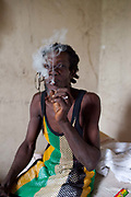 Rastafarian man smoking a joint ganja marihuana in a squatted great house, Cornwall, Jamaica.