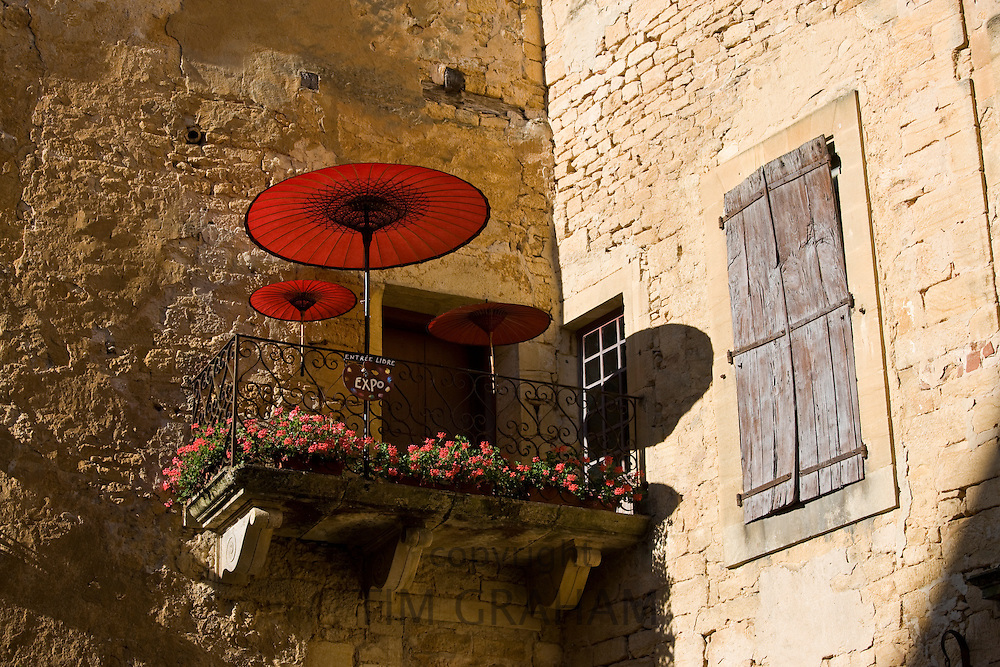 Sun parasols on balcony veranda at gallery in popular picturesque tourist destination of Sarlat in the Dordogne, France