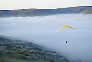 A Paraglider soars form Mam Tor above a misty Edale