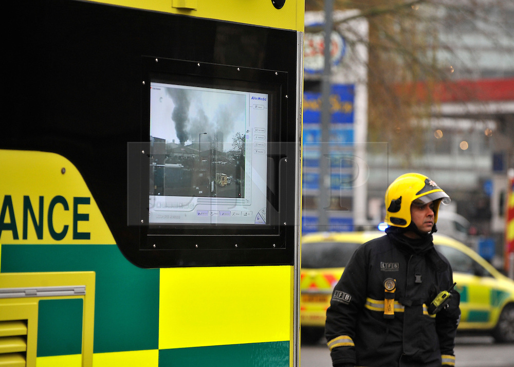 © Licensed to London News Pictures. 31/01/2012, London, UK. Fire officers monitor the situation on a TV screen. A huge fire, thought to be in an old dairy building containing small business is causing road and tube closures in Wood Lane, West London today 31 January 2012.  A large number of Fire Brigade and London Ambulance are in attendance. Photo credit : Stephen Simpson/LNP