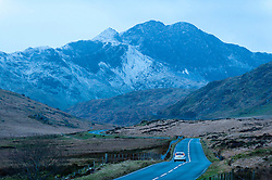 © Licensed to London News Pictures. 30/01/2016. Snowdonia National Park, Gwynedd, Wales, UK. A car travels along the empty A4086 near Capel Curig early this morning. After a mild spell, temperatures dropped to around zero this morning in Snowdonia National Park. A dusting of snow covers the peaks and there is a strong Westerly wind giving a much lower 'feels like' temperature.Photo credit: Graham M. Lawrence/LNP