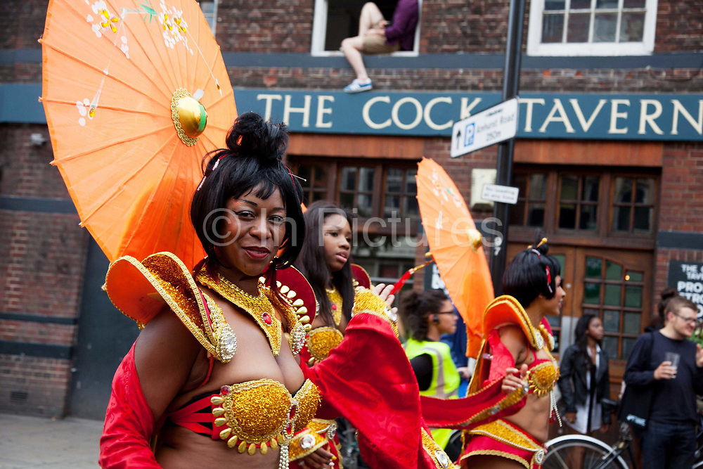Hackney carnival 2014. The procession started in Ridley Road and passed by the The Hackney Town Hall with thousands of spectators lining the road. A smiling black dancer passes the Cock Tavern pub.