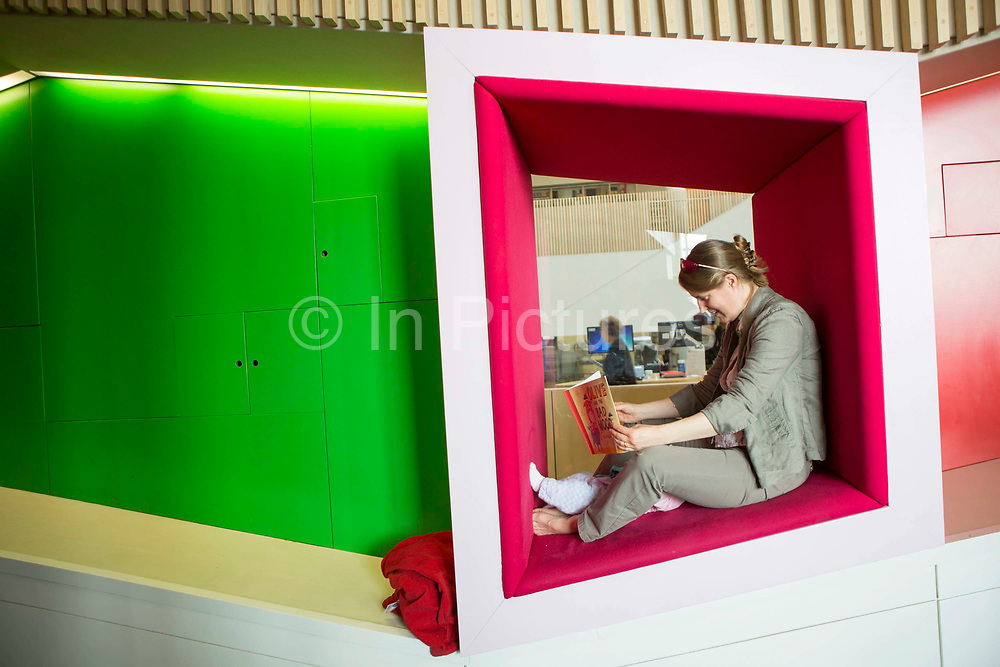 A young mum reading to her child  inside the library of the Hive in Worcester, UK. The first fully integrated university and public library in the UK. It houses the county archives and archaeology service, the local history centre and is also a local authority hub. The building is low energy.