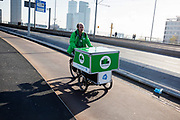 In Rotterdam fietst een bezorger van SuperBuddy voor Albert Heijn over de Erasmusbrug. Met SuperBuddy kunnen boodschappen thuis afgeleverd worden.<br /> <br /> In Rotterdam a messenger of SuperBuddy rides at the Erasmusbrug. SuperBuddy is a messenger service for the daily groceries.