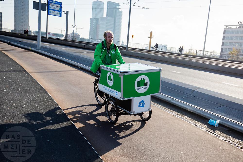 In Rotterdam fietst een bezorger van SuperBuddy voor Albert Heijn over de Erasmusbrug. Met SuperBuddy kunnen boodschappen thuis afgeleverd worden.<br /> <br /> In Rotterdam a messenger of SuperBuddy rides at the Erasmusbrug. SuperBuddy is a messenger service for the daily groceries.