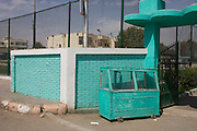 A green-painted food stall and matching background colour of a youth centre in the village of Bairat on the West Bank of Luxor, Nile Valley, Egypt.