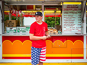 """26 JUNE 2020 - DES MOINES, IOWA: HUNTER (first name only) waits for customers at a booth selling fried potatoes and pork tenderloin sandwiches at Fair Food Friday in Des Moines. The 2020 Iowa State Fair, like many state fairs in the Midwest, has been cancelled this year because of the COVID-19 (Coronavirus) pandemic. The cancellation of the fair left many small vendors stranded with no income. Some of the fair food vendors in Iowa started """"Fair Food Fridays"""" on a property a few miles south of the State Fairgrounds. People drive up and don't leave their cars while vendors bring them the usual midway fare; corndogs, fried tenderloin sandwiches, turkey legs, deep fried Oreos, lemonaide and smoothies. Fair Food Friday has been very successful. The vendors serve 450-500 people per Friday and during the lunch rush people wait in line in their cars 30 - 45 minutes to place an order.    PHOTO BY JACK KURTZ"""