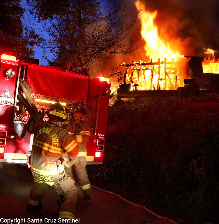 Central Firefighters pull hose from a pumper as they arrive at a fully involed home in the hills over Soquel, California.<br /> Photo by Shmuel Thaler <br /> shmuel_thaler@yahoo.com www.shmuelthaler.com