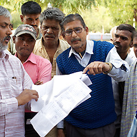 Rupesh (left) discusses the running of the Atri Block State Food Corporation Godown (depot) in Atri with assistant manager  Bharat Rai while local retailers look on...In the course of his work, Rupesh (no surname), advisor to the Indian Supreme Court Commissioner on the right to food, made an unannounced visit to the Atri Block State Food Corporation Godown (depot) in Atri where he unearthed two cases of malpractice. He found that Bharat Rai, assistant manager of the godown, responsible, among other things, for the distribution of one quintel of grain per-month to each of the PDS (Public Distribution System) retailers in his area as part of the Antyodaya scheme (providing staple food for the poorest of the poor), had failed to deliver this essential food for eleven of the previous twelve months. Furthermore, it was discovered that though retailers supplied by the Atri Godown had paid Rai for grains for the months of November and December 2010, these foods had not in fact been delivered. Rupesh demanded paperwork from Bharat Rai and will now take up the case with the District Magistrate in Gaya. Rupesh argues that the only way to properly administer schemes like PDS is to make them universal so that the the educated middle class, and not just the poor, have a personal interest in the running of them...India's PDS (Public Distribution System) is a three-tier system that provides subsidized food at thee different rates for those people classified as APL (Above Poverty Line), BPL (Below Poverty Line) and Antyodaya (literally 'serving the last man in the queue'). The system is an essential provision that sustains the lives of many. However experts including the JSS (Jan Swasthya Sahyog or People's Health Support Group) argue that the PDS needs to be extended. This is because the monthly allocation of subsidized grain will last the average family just 12 days...Rupesh is supported by Oxfam as part of a five month pilot program that began in November 2010...Photo: Tom Piet