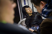 Commuters sleeping on the Tokyo Subway. The subway carries some 8 million passengers a day through 290 stations and over 13 lines. Japan.