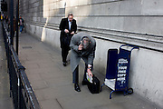 While holding a conversation on his smartphone, a stooping gent struggles to slide a free copy of the Evening Standard newspaper into his briefcase, beneath the high walls of the Bank of England in the City of London.