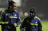 Chico Flores and Nathan Dyer (r) arrive at Swansea city FC team training in Landore, Swansea, South Wales on Wed 19th Feb 2014. the team are training ahead of tomorrow's UEFA Europa league match against Napoli.<br /> pic by Phil Rees, Andrew Orchard sports photography.