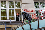 One of two Palestine Action activists is seen being taken by the police through the window following the arrival of the Protest Removal Unit (PRU) outside Elbit Systems HQ office at 77 Kingsway, central London on Friday afternoon, Aug 6, 2021. (VX Photo/ Vudi Xhymshiti)