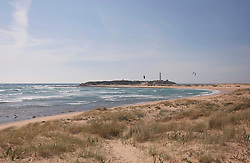 View of lighthouse and kitesurfers at beach near atlantic ocean