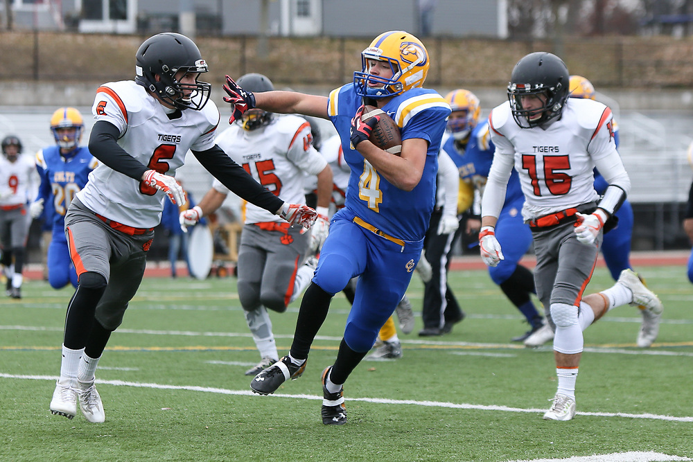 Comp's Corey Heath extends his arm to fend off South Hadley's Jack Dawson during the South Hadley versus Chicopee Comp Thanksgiving football game at Chicopee Comp High School in Chicopee on November 24, 2016. Heath broke the 1,000 yard threshhold for the season during the game. (Chris Marion / The Republican)
