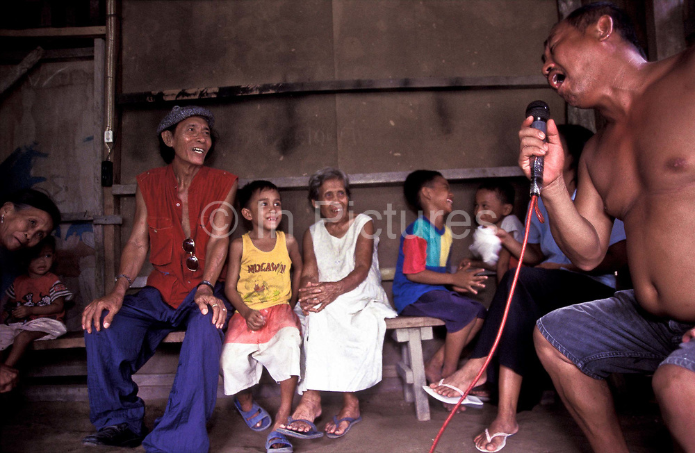 """Babi Baldo and Conrado Barrera sing """"my way"""" and other songs at Boyet's Karaoke bar with children and adults looking on in the small fishing village of Busok Busok, Aurora, Philippines"""