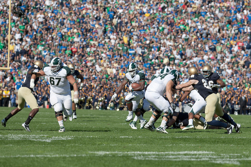Michigan State running back Le'Veon Bell (#24) follows the running lane opened by his offensive lineman in action during NCAA football game between Notre Dame and Michigan State.  The Notre Dame Fighting Irish defeated the Michigan State Spartans 31-13 in game at Notre Dame Stadium in South Bend, Indiana.