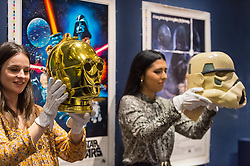 "© Licensed to London News Pictures. 06/12/2019. LONDON, UK. Staff members pose with a ""Return Of The Jedi Promotional C-3PO Helmet"", 1983 (Estimate GBP15,000-20,000) and a ""Prototype Imperial Stormtrooper Helmet"", 1976 (Estimate GBP30,000-60,000) in front of movie posters at the preview of ""Star Wars Online"", a sale dedicated to Star Wars collectibles encompassing 100 lots from the franchise.  Sotheby's will host the online-only sale which will run until 13 December, ahead of the final film in the sequel trilogy ""Star Wars: The Rise of Skywalker"".  Highlights from the sale are on display at Sotheby's New Bond Street 6 to 11 December.   Photo credit: Stephen Chung/LNP"