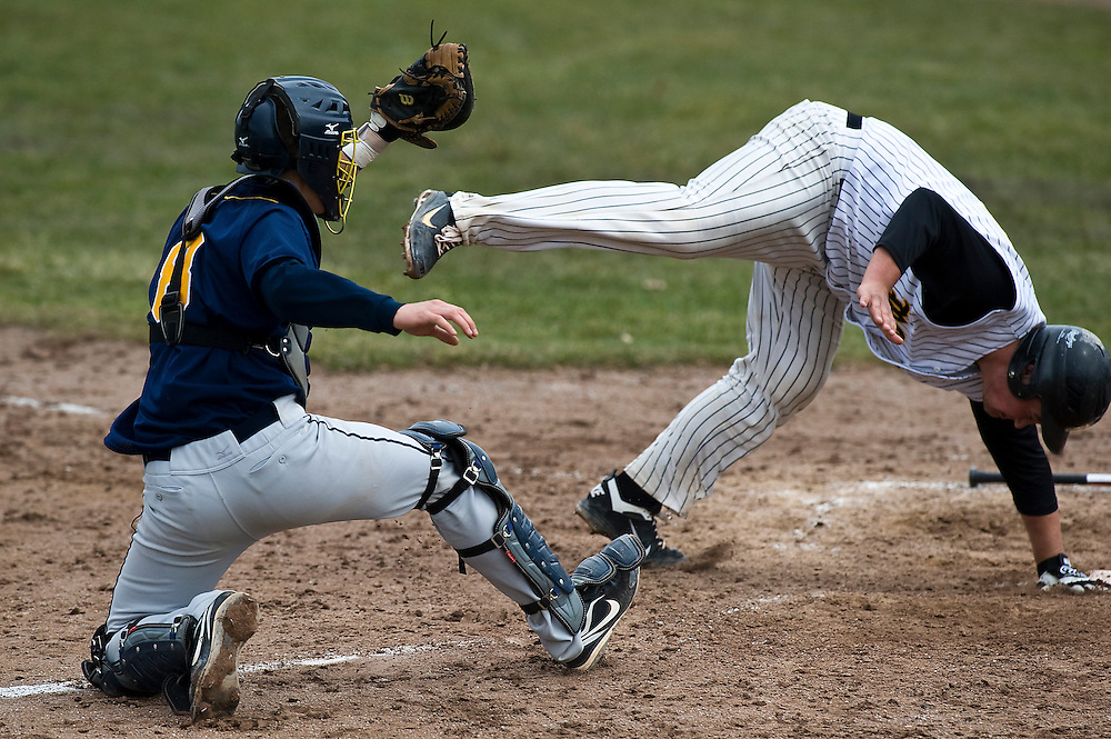 Matt Dixon | The Flint Journal..St. Clar catcher Devon Wiegers tags out Mott Runner Coty Swinson in Mott's conference home-opener at Broome Park in Flint Friday afternoon.Mott defeated St. Clair 6 to 5 in the bottom of the eighth inning.