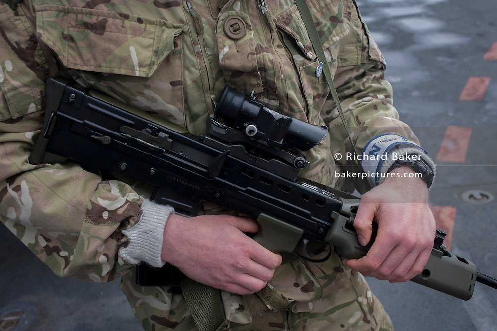 "A detail of the arms of a Royal Marines Commando guarding the top deck of HMS Illustrious during a tour by the general public on-board the Royal Navy's aircraft carrier in Greenwich. The weapon is an SA80 (Small Arms for the 1980s) a British family of 5.56mm small arms. It is a selective fire, gas-operated assault rifle. The Royal Marine Corps (RM) is the marine corps and amphibious infantry of the United Kingdom and forms part of the Naval Service (along with the Royal Navy, Royal Fleet Auxiliary and associated organisations). The Royal Marines were formed in 1755 as marine infantry for the Royal Navy. However, it can trace its origins back to the formation of ""the Duke of York and Albanys maritime regiment of foot"" at the grounds of the Honourable Artillery Company on 28 October 1664"