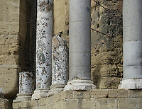Grey partly broken stone columns stand in front of the beige stage wall at the 1st Century Roman Theater in Orange, Provence, France. Seating up to 6,000 spectators in ancient Roman times, the Roman Amphitheater is now a UNESCO World heritage site.