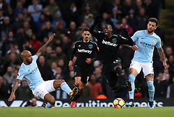 """Manchester City's Fabian Delph (left) and Kyle Walker (right) battle for the ball with West Ham United's Pedro Obiang (centre) during the Premier League match at the Etihad Stadium, Manchester. PRESS ASSOCIATION Photo. Picture date: Sunday December 3, 2017. See PA story SOCCER Man City. Photo credit should read: Martin Rickett/PA Wire. RESTRICTIONS: EDITORIAL USE ONLY No use with unauthorised audio, video, data, fixture lists, club/league logos or """"live"""" services. Online in-match use limited to 75 images, no video emulation. No use in betting, games or single club/league/player publications."""