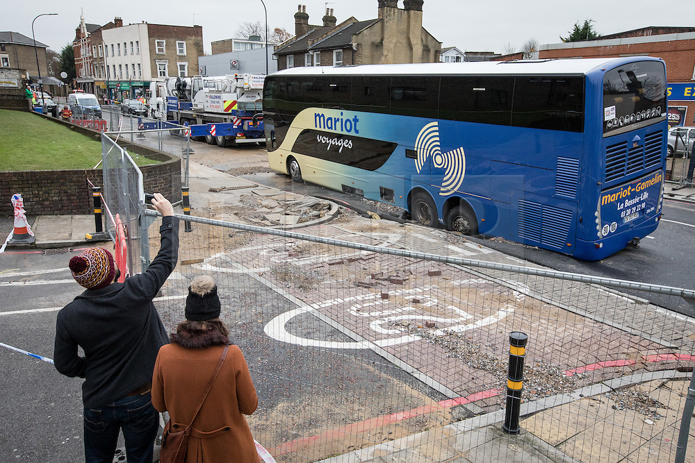 © Licensed to London News Pictures. 27/11/2016. London, UK. Passersby take photographs of a French tourist coach which sits stranded after it fell into a sinkhole in Lewisham. Lee High Road has been closed off and police declared a 'major incident' after the coach with 100 passengers on board fell into a sinkhole caused by a burst water mains, flooding a long stretch of the road including many local businesses. . Photo credit: Rob Pinney/LNP