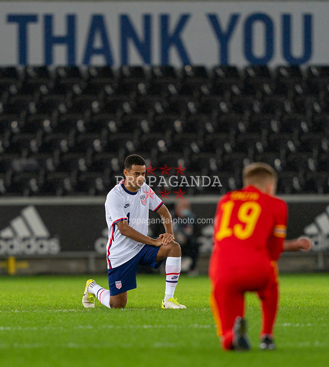 SWANSEA, WALES - Thursday, November 12, 2020: USA's Tyler Adams kneels down (takes a knee) in support of the Black Lives Matter movement before an International Friendly match between Wales and the USA at the Liberty Stadium. (Pic by David Rawcliffe/Propaganda)