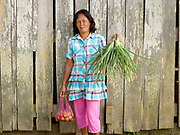 "Helen Jawil, a member of the ""Women's Rural Improvement' group with her garden produce in Sitio Matinao, Alamada, Cotabato province, Mindanao Island, The Philippines. In the Philippines climate change is contributing to an increase in the frequency and intensity of typhoons as well as a general rise in temperatures and rain leading to an increase in droughts, flash floods and landslides. This is having a huge impact on smallholder farmers who depend on one cash crop leaving them vulnerable to any changes in weather patterns. If their crops fail they are left with no other source of income for that year. In central Mindanao Oxfam is working with local partners and governments to increase awareness of climate change in poor communities and reduce the risks it creates to vulnerable farmers by supporting them in crop diversification."