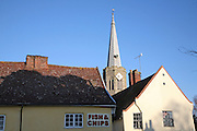 Church spire viewed over fish and chips shop, Wickham Market, Suffolk, England