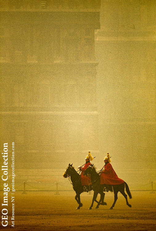 Two mounted Queen's Life Guards in red capes brighten a foggy morning.