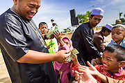 A man hands out cash as a gift to children after Eid services at Songkhla Central Mosque in Songkhla province of Thailand. Eid al-Fitr is also called Feast of Breaking the Fast, the Sugar Feast, Bayram (Bajram), the Sweet Festival and the Lesser Eid, is an important Muslim holiday that marks the end of Ramadan, the Islamic holy month of fasting.