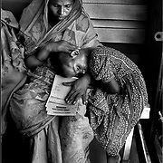 Woman and child wait to see doctor. Bengalis travel for miles to see physicians on the Lifebuoy Friendship Hospital on the Brahmaputra River in Northern Bangladesh. The ship patrols the far reaches of char-based populations where no permanent medical infrastructures are set  up due to annual flooding. The ship offers primary and secondary health-care services and is staffed by prominent local and international doctors. This was one of many assignments I completed on contract in Bangladesh for the Canadian International Development Agency.   (Leica M6  with 24 mm lens)