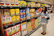 The Qureshi family of Lorenskog, Norway, an Oslo suburb. Pritpal Qureshi, 49, choosing cereal in a supermarket in Oslo while buying a week's worth of groceries. Model-Released.
