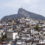A view from Santa Teresa in the hills of Rio de Janeiro as The iconic Cristo Redentor, Christ the Redeemer statue sits atop the mountain Corcovado. In the foreground is the Favela Morro da Coroa. Many favela's scatter the hillsides around Rio while The iconic statue of Christ can be seen for miles around the city. Rio de Janeiro, Brazil. 20th September 2010. Photo Tim Clayton..