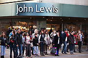 Shoppers await to cross Oxford Street by John Lewis, the famous department store.