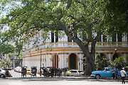 Steet scene with classic car, horse and carriage and rickshaws in downtown Habana Vieja, Havana, Cuba