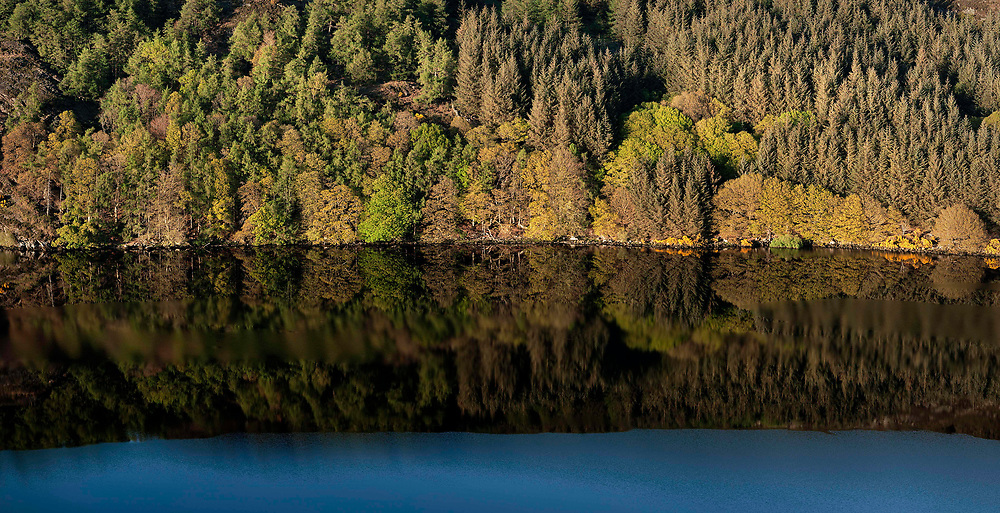 When calm, the deep black waters of Lough Dan, Co.Wicklow can provide spectacular opportunities for photography. Here, a reflection of the lakeshore woodland at sunset.