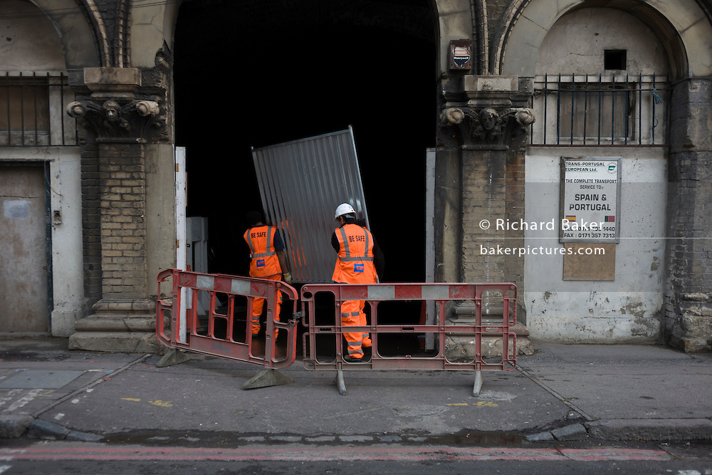 Workmen carry metal sheeting into dark tunnel of railway arches.