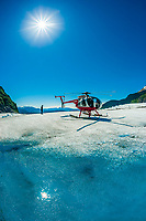 Helicopter landed near azure blue meltwater pools on the Mendenhall Glacier, near Juneau, Alaska USA.