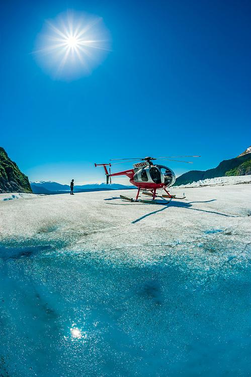 Helicopter landed near azure blue meltwater pools on the Mendenhall Glacier, near Juneau, Alaska USA.