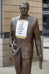 © Licensed to London News Pictures; 15/05/2021; Bristol, UK. A protest placard for #NHSPayProtest and #NHSSayNo is seen on the statue of Cary Grant in Millennium Square in the city centre. NHS workers are campaigning for a better pay rise and are urging everyone who clapped for the NHS staff a year ago to support them. The demonstration is being organised by the Bristol branch of a national group called NHS Workers Say No, which was set up away from the main staff unions to call for a 15 per cent pay rise for all NHS staff to make up for being left out of a one-off pay rise for public sector workers as a reward for their efforts during the covid coronavirus pandemic. Photo credit: Simon Chapman/LNP.