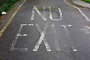 The word NO EXIT fading on a south London housing estate road surface. We see a detail of the ground, where the stencil has been painted a while ago, now fading after years of weathering as well as weeds now growing from old tarmac. The estate is in the London borough of Southwark, a mile or so south of the river.
